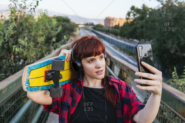 Redhead woman with skateboard taking selfie while standing on footbridge