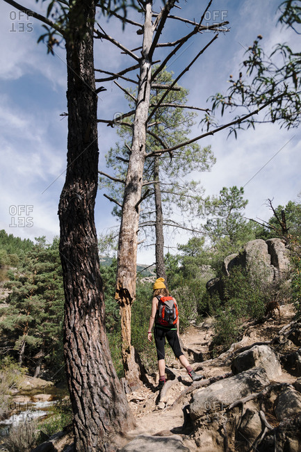 Female trekker with backpack walking on rock path in forest at La Pedriza- Madrid- Spain