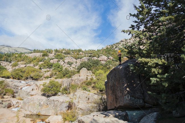 Female trekker admiring view while standing on large rock in forest at La Pedriza- Madrid- Spain