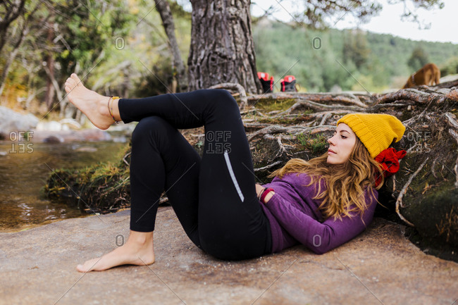 Woman wearing knit hat lying down by river in forest at La Pedriza- Madrid- Spain