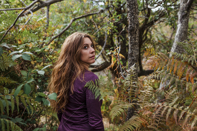 Woman looking away while walking between plant in forest at La Pedriza- Madrid- Spain