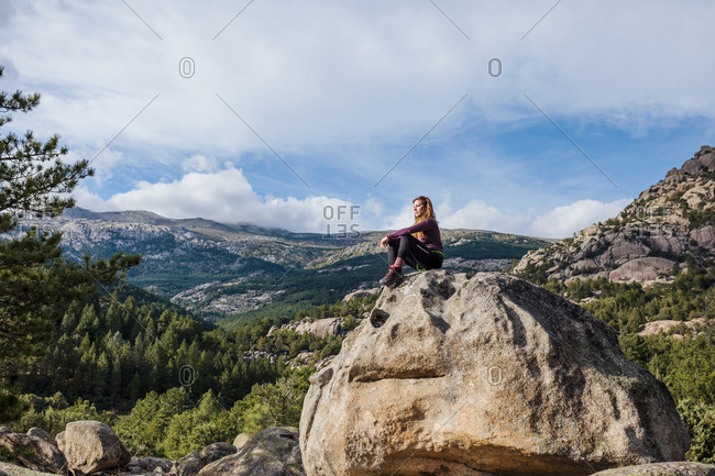 Trekker looking at view while sitting on rock against sky at La Pedriza- Madrid- Spain