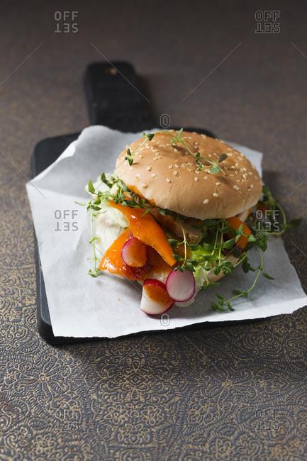 Vegan burger with soy schnitzel strips- bell pepper- radishes- oregano and lettuce