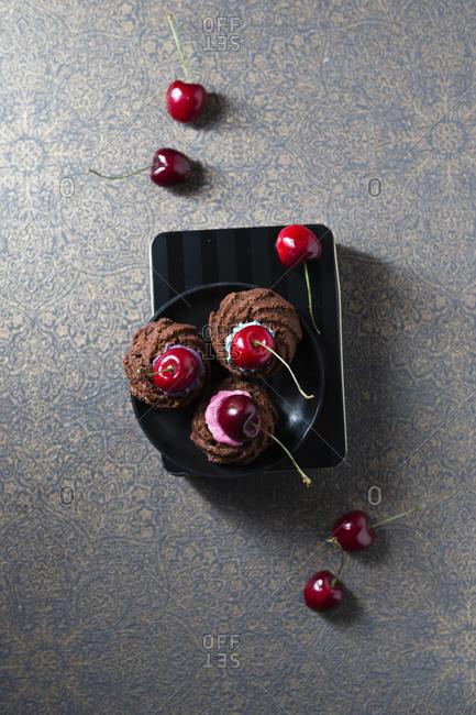 Mini gugelhupfwith colorful cake cream and cherries