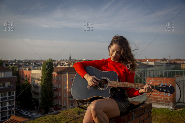 Young woman playing guitar while sitting on rooftop in city