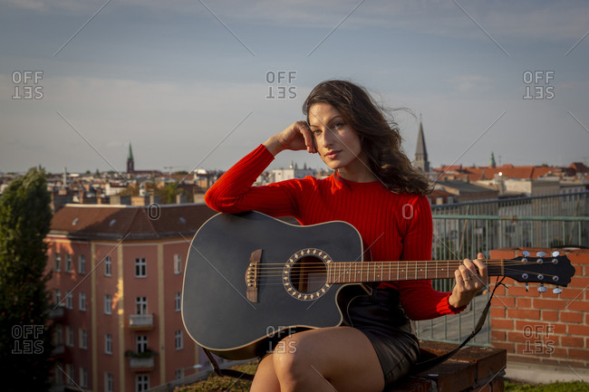 Thoughtful young woman sitting on rooftop with guitar in city