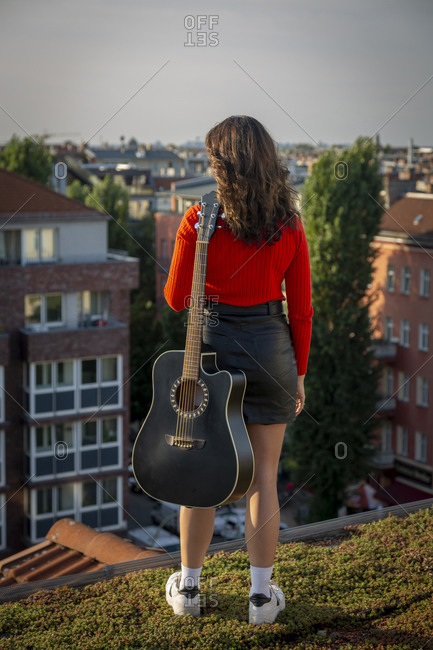 Young woman with guitar standing on rooftop