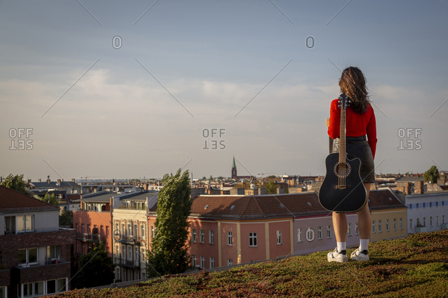 Young woman carrying guitar while standing on rooftop against sky