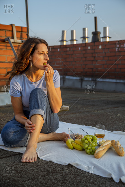 Young woman having fruits during picnic on rooftop
