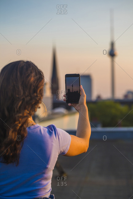 Woman photographing through smart phone while standing on rooftop
