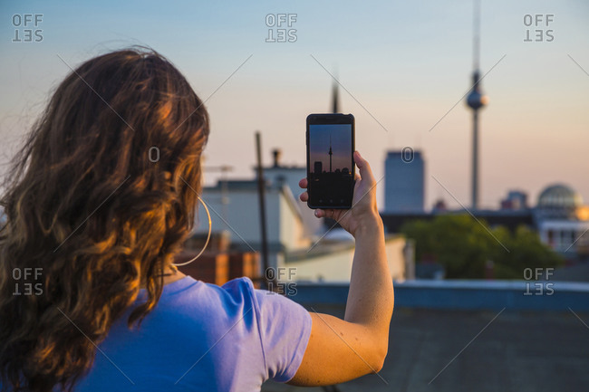 Woman photographing through smart phone while standing on rooftop during sunset
