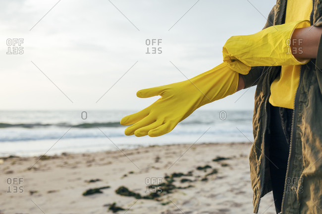 Woman standing and wearing protective glove for cleaning beach against sky