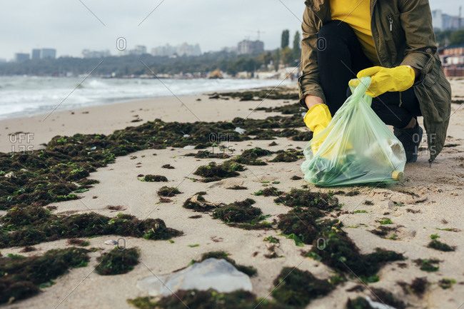 Environmentalist collecting garbage in garbage bag while crouching at beach