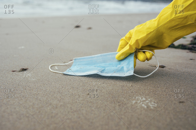 Female environmentalist picking up face mask while cleaning beach