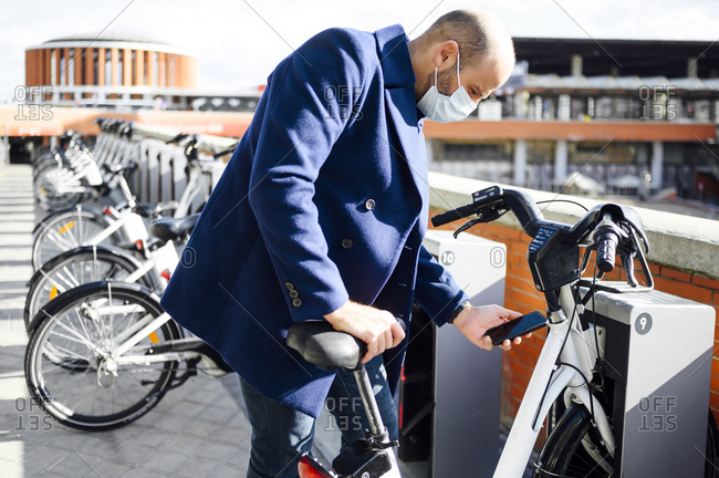 Man wearing protective face mask unlocking bicycle through smart phone on sunny day