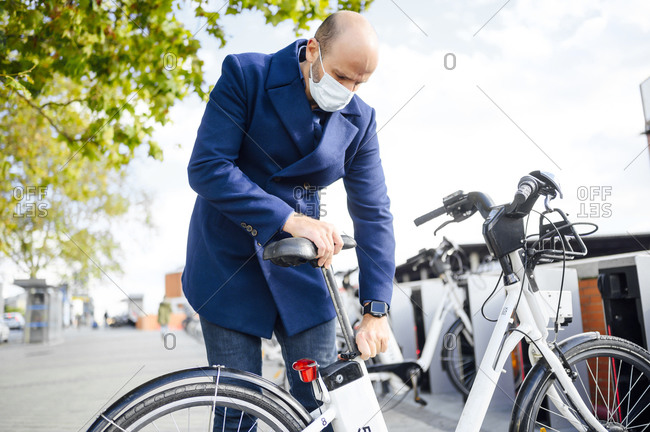 Man with protective face mask adjusting electric bicycle seat while standing on footpath in city during sunny day