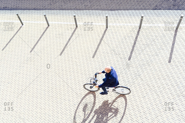 Mature man cycling on sunny day during pandemic illness