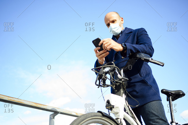 Mature man using smart phone while standing with bicycle against blue sky on sunny day during coronavirus
