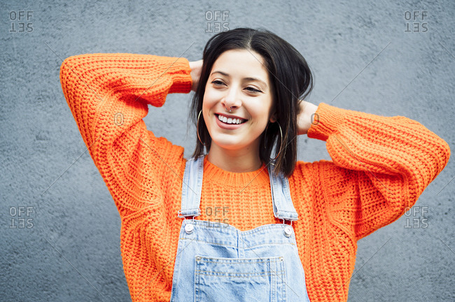 Smiling woman wearing orange sweater looking away while standing against gray wall