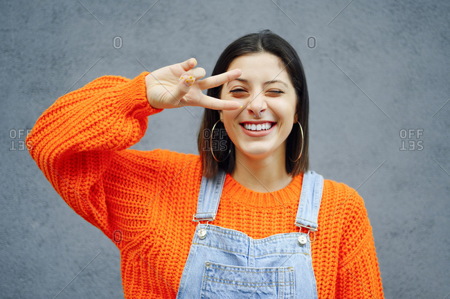 Young woman showing peace sign while standing against gray wall