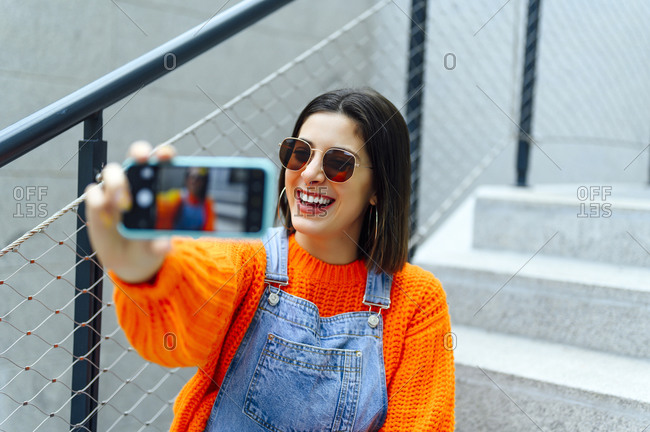 Smiling woman taking photo of herself through smart phone while sitting on staircase