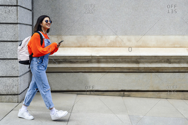 Smiling woman with backpack using mobile phone while walking against wall