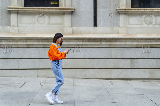 Young woman using mobile phone while walking against wall on footpath
