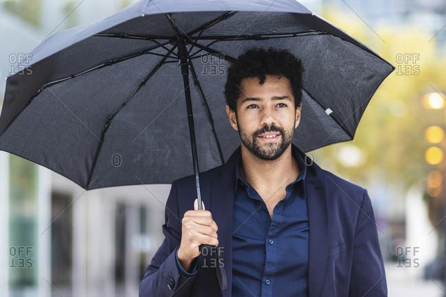 Smiling entrepreneur holding umbrella in city during rainy season