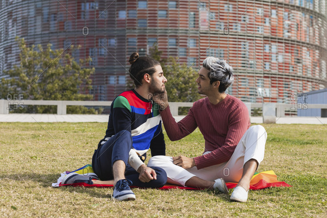 Affectionate man looking at partner while sitting in park