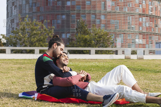 Affectionate man embracing partner while sitting in park