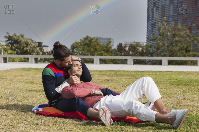 Affectionate man embracing partner while sitting in park against rainbow