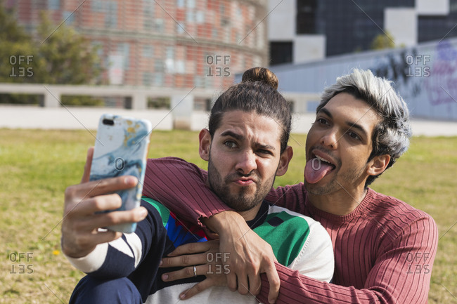 Man with male partner sticking out tongue while taking selfie through smart phone in park