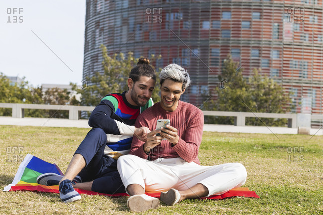 Smiling man with gay partner using mobile phone in park