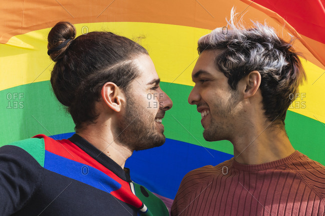Smiling affectionate man looking at male partner against rainbow scarf