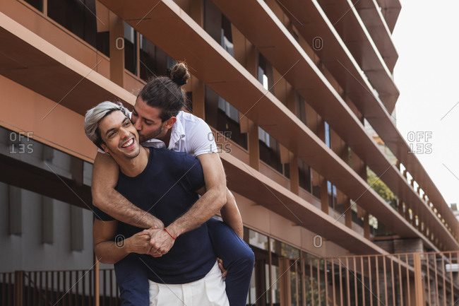 Man piggybacking gay partner while looking away against building in city