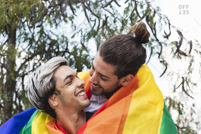 Smiling affectionate man with rainbow scarf looking at male partner against tree
