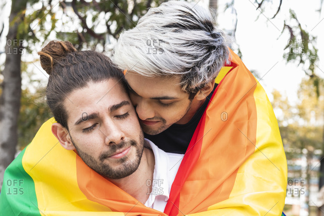 Affectionate man with rainbow scarf embracing male partner against tree