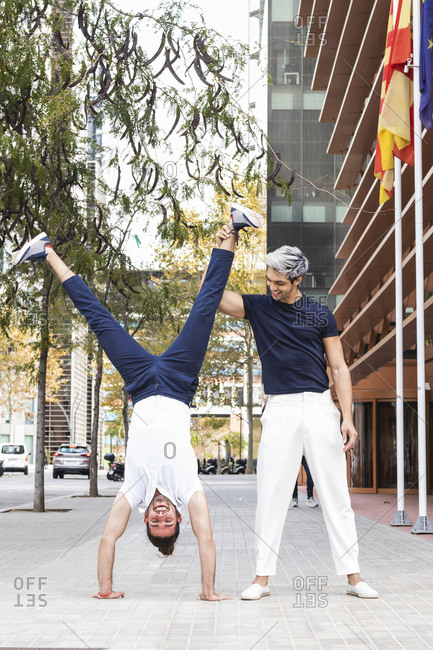 Smiling man practicing handstand by male partner in city
