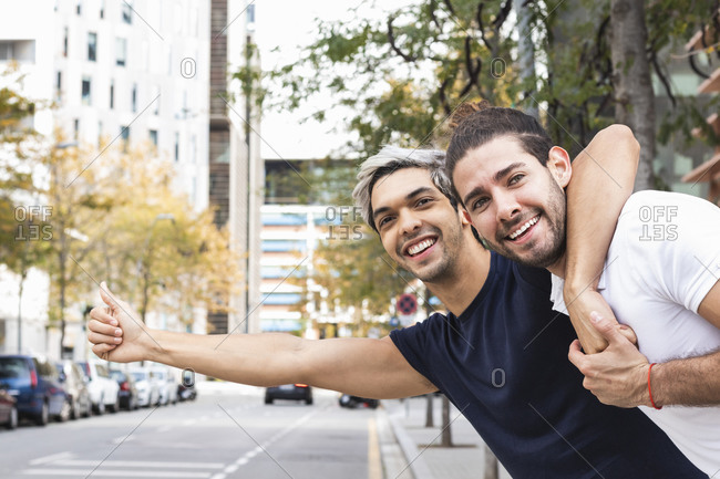Smiling homosexual couple hailing a ride in city