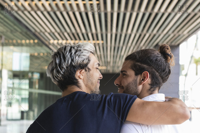 Smiling man with arm around looking at gay partner in city