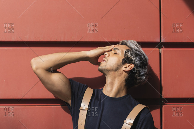 Young man with eyes closed standing against red wall