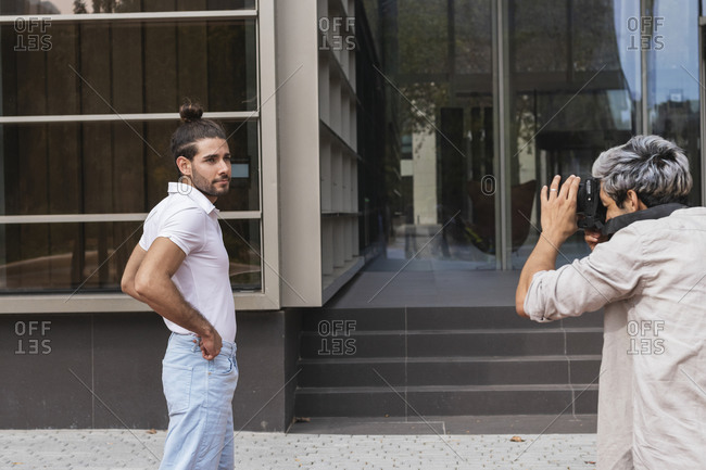 Man photographing gay partner through camera in city