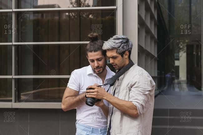 Man and gay partner looking at camera in city