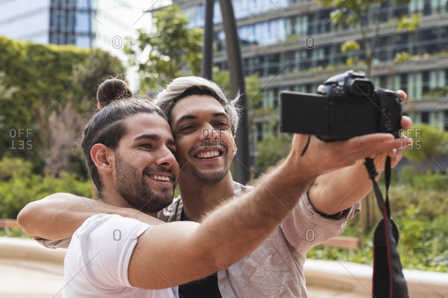 Smiling gay couple photographing through camera in city