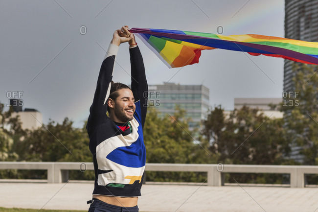 Smiling man with eyes closed holding rainbow scarf against sky
