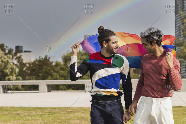 Smiling affectionate man with rainbow scarf looking at male partner in public park