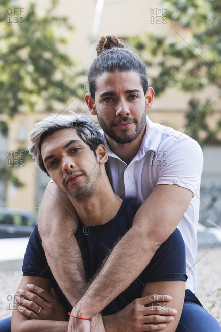 Confident man with male partner sitting in city