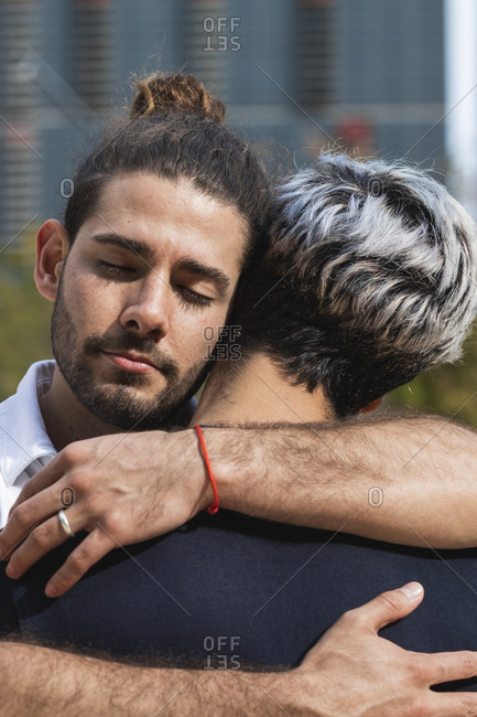 Man with eyes closed embracing partner in park during sunny day