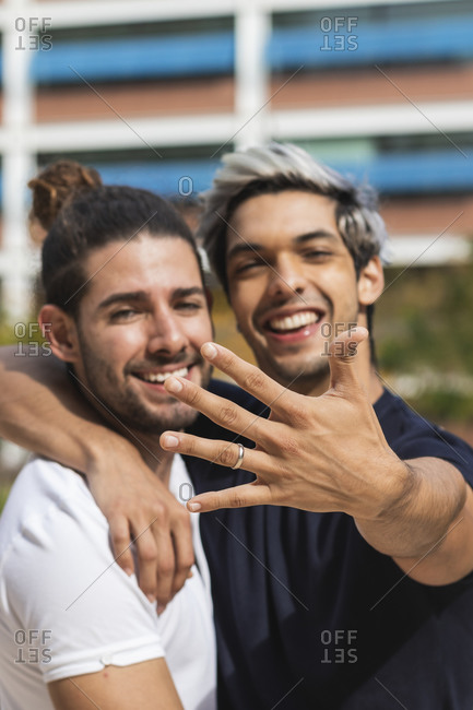 Smiling man showing engagement ring while standing by male partner in park