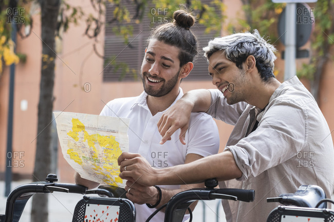Smiling gay couple looking at map in city